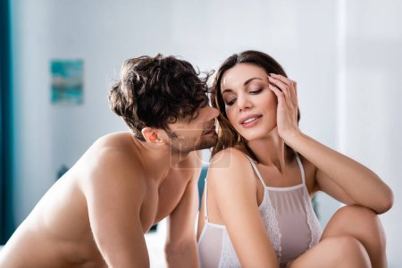 Photo for Handsome shirtless man looking at beautiful smiling girlfriend at home - Royalty Free Image