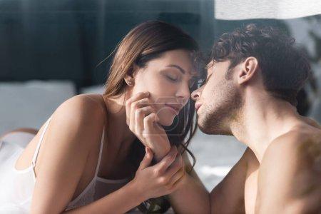 Photo pour Concentration sélective de l'homme torse nu embrasser et toucher le visage de la femme attrayante dans la chambre - image libre de droit