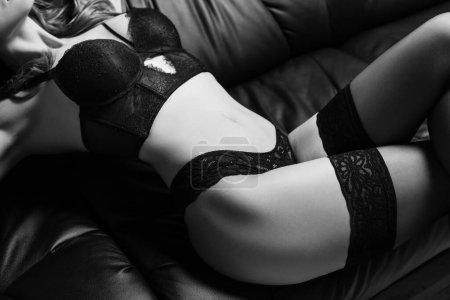 Photo pour Image monochrome de femme sensuelle en lingerie dentelle et bas couchés sur le canapé - image libre de droit
