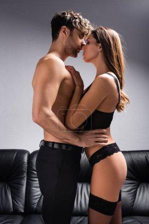 Photo pour Vue latérale de l'homme torse nu embrassant femme sensuelle en lingerie et bas sur gris - image libre de droit
