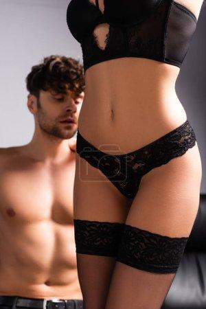 Photo pour Focus sélectif de la femme sensuelle en lingerie et bas debout près de copain torse nu sur gris - image libre de droit