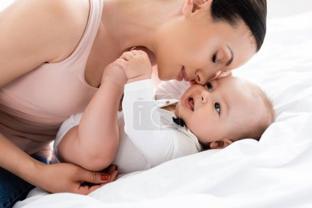 Photo for Attractive mother with closed eyes near cute infant son on bed - Royalty Free Image