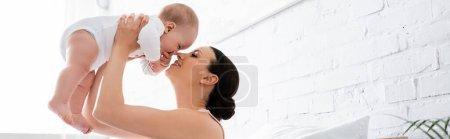 Photo pour Concept panoramique de mère heureuse tenant dans les bras fils bébé mignon dans la chambre - image libre de droit