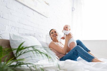 Photo pour Foyer sélectif de mère heureuse en jeans assis sur le lit et tenant dans les bras fils bébé mignon - image libre de droit