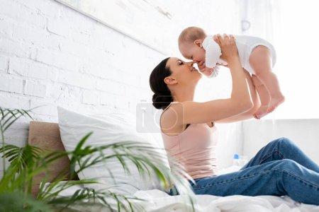 Photo pour Foyer sélectif de la mère gaie en jeans assis sur le lit et tenant dans les bras fils bébé mignon - image libre de droit