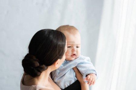 Photo pour Mère tenant dans les bras mignon enfant fils en vêtements de bébé - image libre de droit