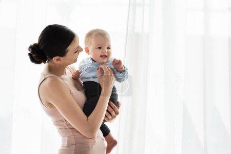 Photo pour Souriant mère tenant dans les bras mignon enfant fils en vêtements de bébé - image libre de droit