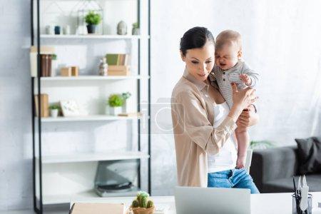 Photo pour Freelance tenant dans les bras pleurer bébé fils et regardant ordinateur portable - image libre de droit
