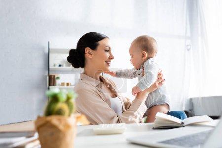 Selektiver Fokus einer glücklichen Mutter, die ihren kleinen Sohn in der Nähe des Notebooks betrachtet
