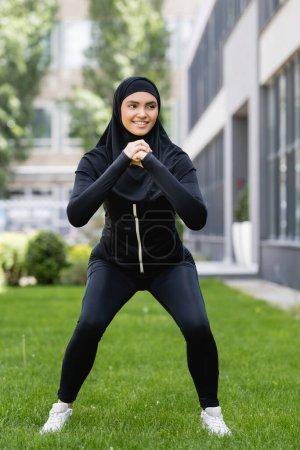 Photo pour Heureuse fille musulmane avec les mains serrées exerçant sur l'herbe - image libre de droit