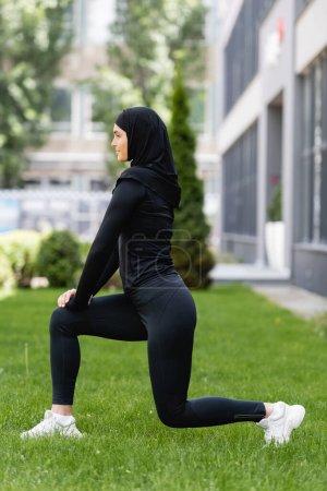 Photo pour Vue latérale de la fille musulmane qui fait des fentes sur l'herbe verte - image libre de droit