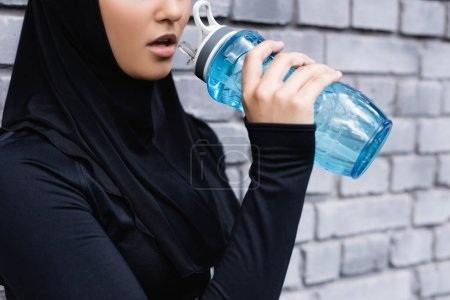 Photo for Cropped view of young muslim sportswoman in hijab holding sports bottle with water outside - Royalty Free Image