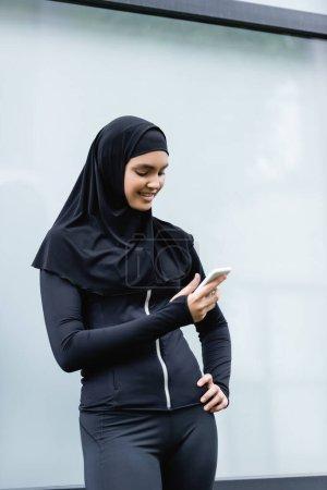 Photo pour Femme musulmane heureuse utilisant smartphone et debout avec la main sur la hanche - image libre de droit