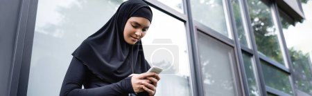 Photo for Website header of young muslim woman using smartphone - Royalty Free Image