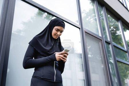Photo pour Vue à faible angle de la jeune femme musulmane en utilisant un smartphone - image libre de droit