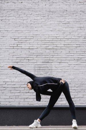 Photo pour Femme sportive arabe en hijab faisant de l'exercice près d'un mur de briques - image libre de droit