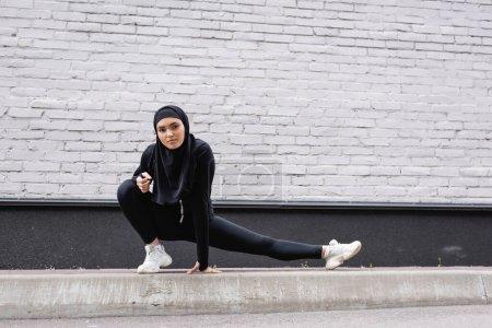 Photo pour Femme sportive arabe en hijab s'étirant près du mur de briques - image libre de droit