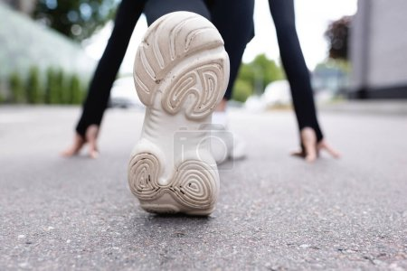 Photo for Close up of white sneakers of sportswoman exercising on asphalt - Royalty Free Image