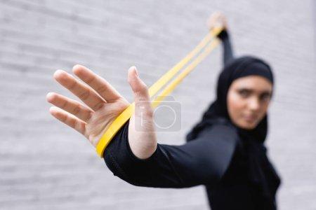 Photo pour Foyer sélectif de la sportive arabe dans le hijab exercice avec bande de résistance près du mur de briques - image libre de droit