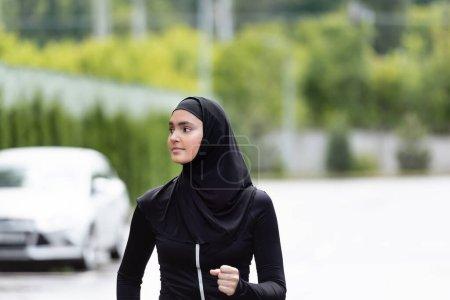 Photo pour Femme de sport arabe en hijab et vêtements de sport jogging et détournement des yeux - image libre de droit