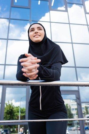 Photo pour Foyer sélectif de femme musulmane heureuse en hijab debout avec les mains serrées près du bâtiment moderne - image libre de droit