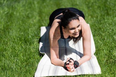 cheerful sportswoman doing plank on fitness mat outside