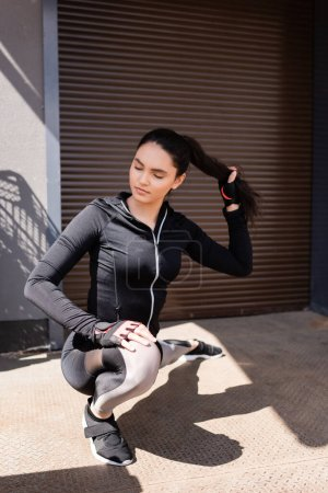 selective focus of beautiful young sportswoman stretching outside while touching hair