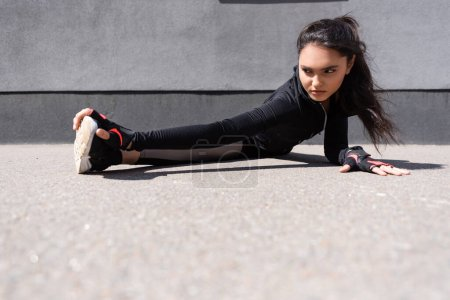 selective focus of beautiful young sportswoman stretching on asphalt