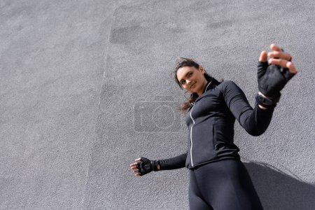 Photo for Low angle view of happy young sportswoman smiling near concrete wall - Royalty Free Image