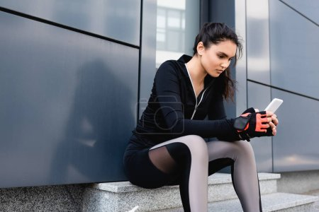 Photo for Young sportswoman sitting and using smartphone outside - Royalty Free Image