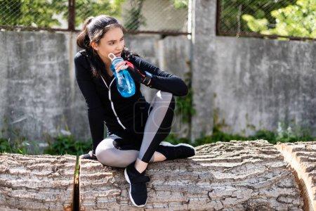 Photo pour Fille en sportswear noir tenant bouteille de sport avec de l'eau et assis sur le tronc d'arbre - image libre de droit
