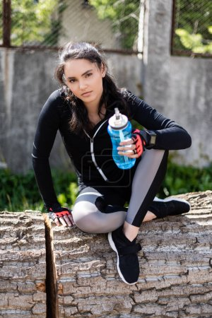 girl in sportswear holding sports bottle with water and sitting on tree trunk