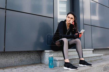 junge Sportlerin sitzt neben Sportflasche und hält Smartphone