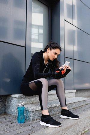 junge Sportlerin sitzt neben Sportflasche und benutzt Smartphone