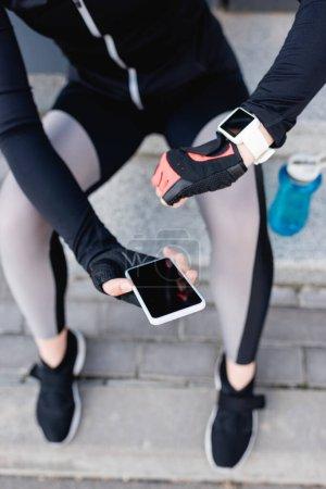 Photo pour Vue recadrée d'une sportive avec tracker de fitness à portée de main avec smartphone et écran vierge - image libre de droit