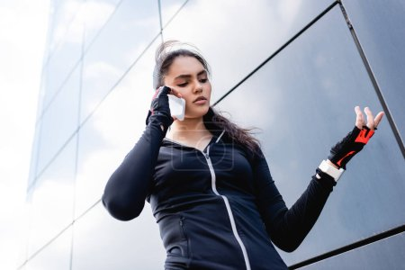 low angle view of young sportswoman gesturing while talking on smartphone