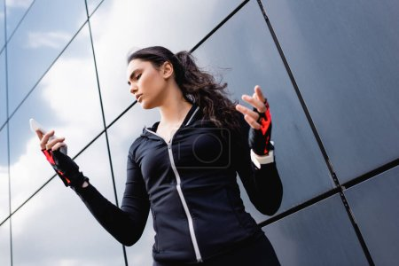low angle view of young sportswoman gesturing while looking at smartphone