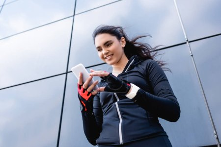 Photo for Low angle view of happy sportswoman looking at smartphone - Royalty Free Image