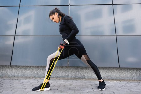 beautiful young sportswoman exercising with resistance band