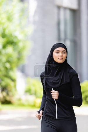 Photo pour Jeune sportive arabe en hijab courant dehors - image libre de droit