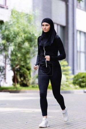 Photo pour Jeune sportive arabe en hijab et vêtements de sport courir à l'extérieur - image libre de droit
