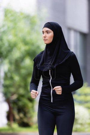 Photo pour Jeune sportive arabe en hijab et vêtements de sport jogging à l'extérieur - image libre de droit