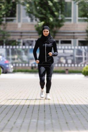 Photo pour Jeune sportive arabe dans le hijab et le jogging de vêtements de sport dans la rue - image libre de droit