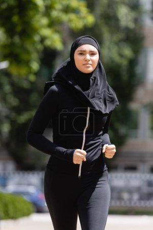 Photo pour Jeune fille arabe en hijab et vêtements de sport jogging à l'extérieur - image libre de droit