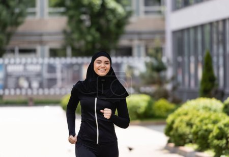 Photo pour Souriant arabian fille dans hijab et sportswear jogging à l'extérieur - image libre de droit