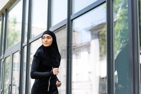 Photo pour Arabian fille dans hijab et sportswear jogging près de bâtiment - image libre de droit