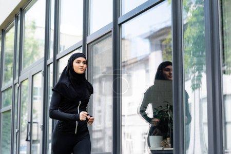 Photo pour Arabe femme en hijab et vêtements de sport jogging près du bâtiment - image libre de droit