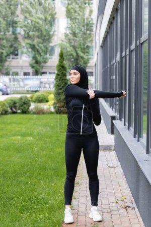 Photo pour Arabe femme en hijab et vêtements de sport travaillant près du bâtiment et de l'herbe verte - image libre de droit