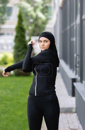 Photo pour Arabe fille en hijab et vêtements de sport travaillant près du bâtiment et de l'herbe verte - image libre de droit