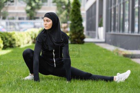 Photo pour Femme arabe flexible en hijab et vêtements de sport s'étendant sur l'herbe verte - image libre de droit